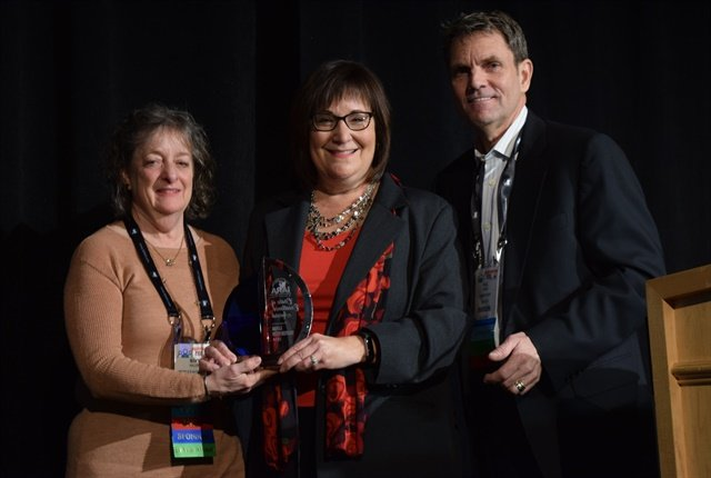 Linda Silverstein accepts her award. Paul Seger and Mary Haller presented the award. Photo by Andy Lundin.