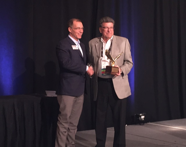 Brown (left) presents the Industry Leadership award from Bobit Business Media to Kennedy (right.)