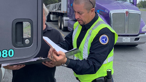 An inspector shows a driver how to transfer his hours of service log at roadside – something...