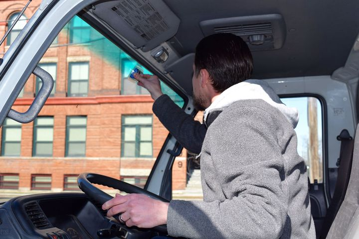 A Bestpass employee installs a toll transponder in a fleet vehicle.