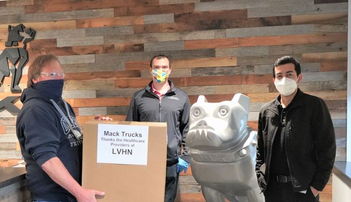 LVO employees William Kulnis (left) and Karan Arora (right) presented face shields to Lehigh Valley Health Network representative Adam Selmasska (center). - Photo: Mack Trucks