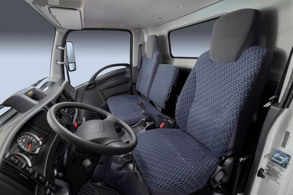 The interior of the 2022i Isuzu N-Series comes with seating surfaces covered in a gray and blue cross-pattern tricot fabric, along with darker gray accents on the steering wheel, gear shift lever, parking brake lever and other controls. - Photo courtesy of Isuzu Commercial Truck of America.