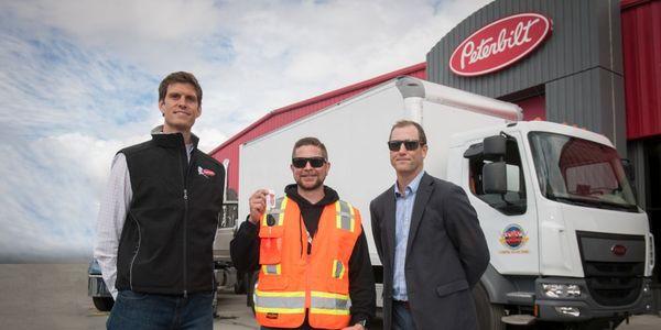 Handing off the keys (L-R)are Chris Devine, CEO, Peterbilt of Alaska; Mark Spafford, General...