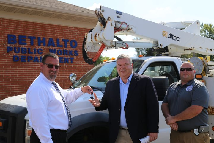 Ameren Illinois Division Director Jason Klein (left) hands the keys to a 2009 Ford F-550 bucket truck to Village of Bethalto Mayor Alan Winslow. Tim Brown (right) Building and Zoning Administrator, reached out to Ameren Illinois to request the donation of a truck.