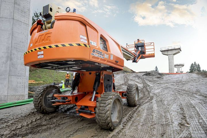 The 670SJ is engineered to automatically adapt to terrain on slopes up to 10 degrees in any direction, while driving with full functionality at a 67 ft. platform height. - Photo: JLG