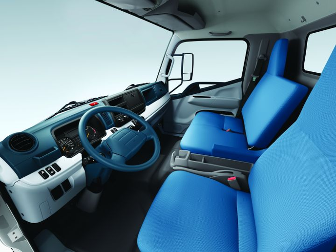 The FE/FG Series was specifically designed to provide a car-like interior. The passenger seats can fold down to form a work area for the driver, and extra storage compartments have been added in the cab area.  - Photo courtesy of Mitsubishi Fuso