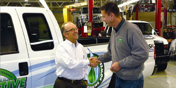 Eric Hansen, founder and president of Competitive Lawn Care, takes delivery of the first...