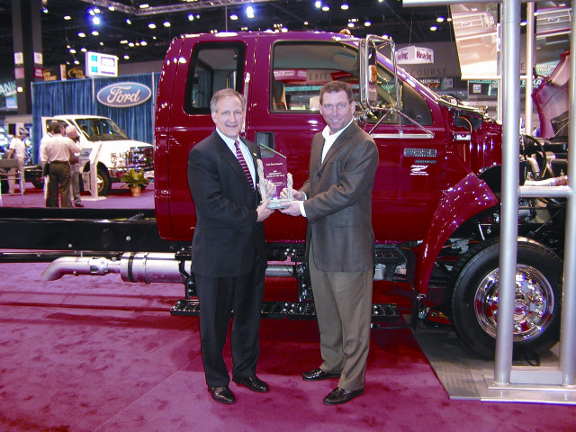Len Deluca (left), director of Ford Commercial Trucks, sales and marketing accepts the Medium-Duty Truck of the Year award from Work Truck magazine Associate Publisher Bob Brown at the National Truck Equipment Association's 2009 Work Truck Show in Chicago. -