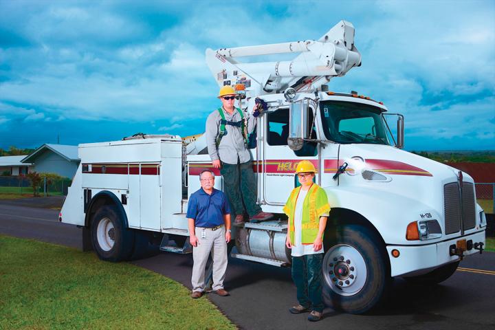 (L-R) Kelvin Kohatsu, Hawaii Electric Light fleet administrator; Joshua Kunimura, Hawaii Electric Light apprentice service lineman; and Clyde Kunimura, Hawaii Electric Light senior service lineman stand on and next to a Kenworth T300 bucket truck. (PHOTO: Zonar) -