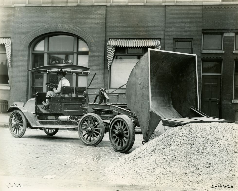 A slope hood International model with a heavy-dump upfit dropping a load of gravel.